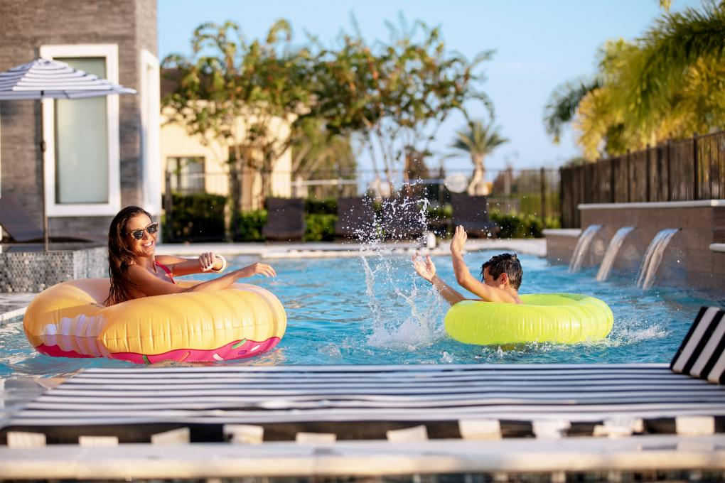 Woman and child on inflatable rings at the pool splashing