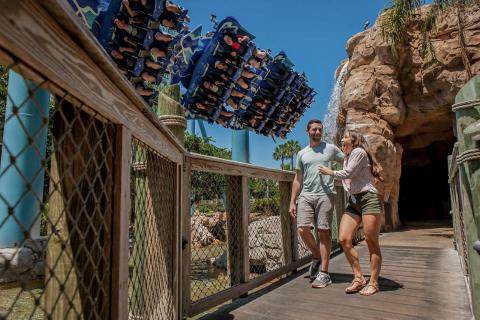 Couple at a theme park, walking on bridge with roller coaster in background