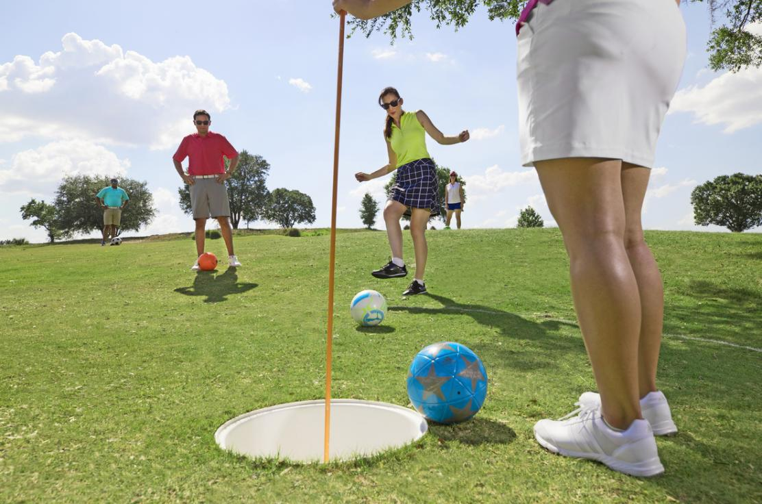 putting footgolf ball into the hole