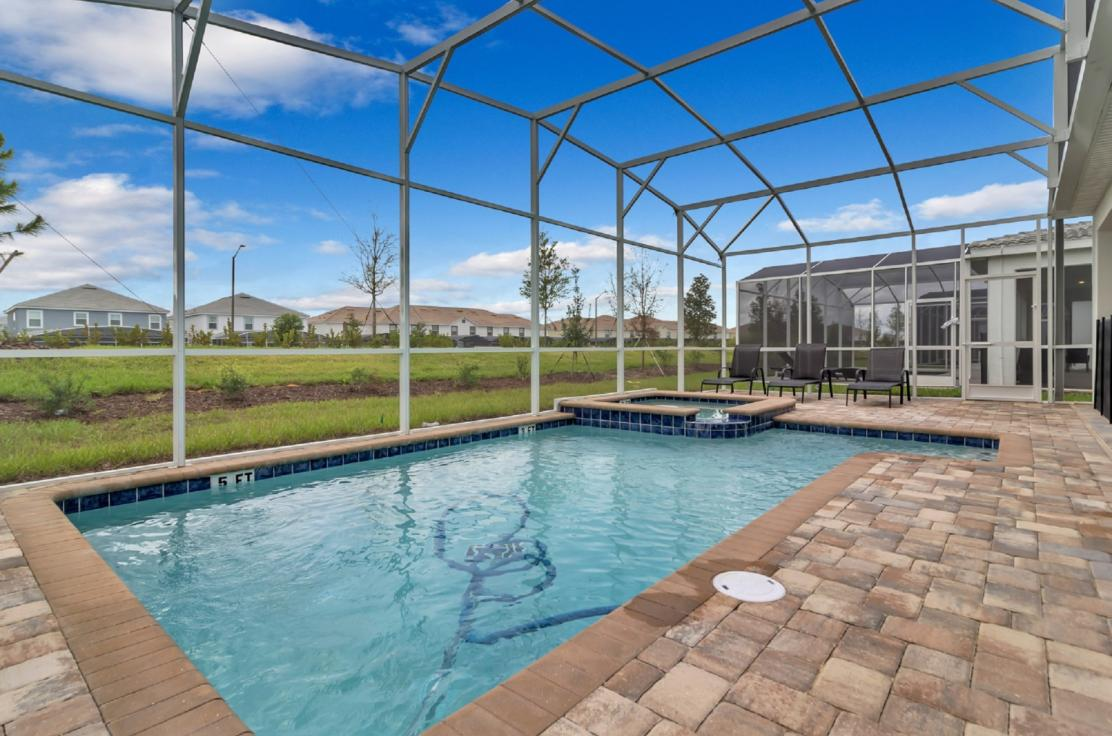Screened in pool area, pool has a small hot tub, there are also lounge chairs beside the pool.