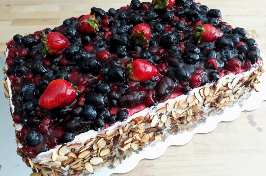 Large sheet cake with fruit preserve filling, topped with a light cream and mixed fresh berries