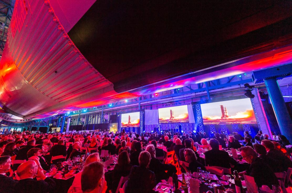 Dinner & celebration for 1000 guests and dignitaries underneath the Apollo 11 Rocket.  A brilliantly lit room with a custom lighted stage, covered in a shiny black vinyl floor covering.