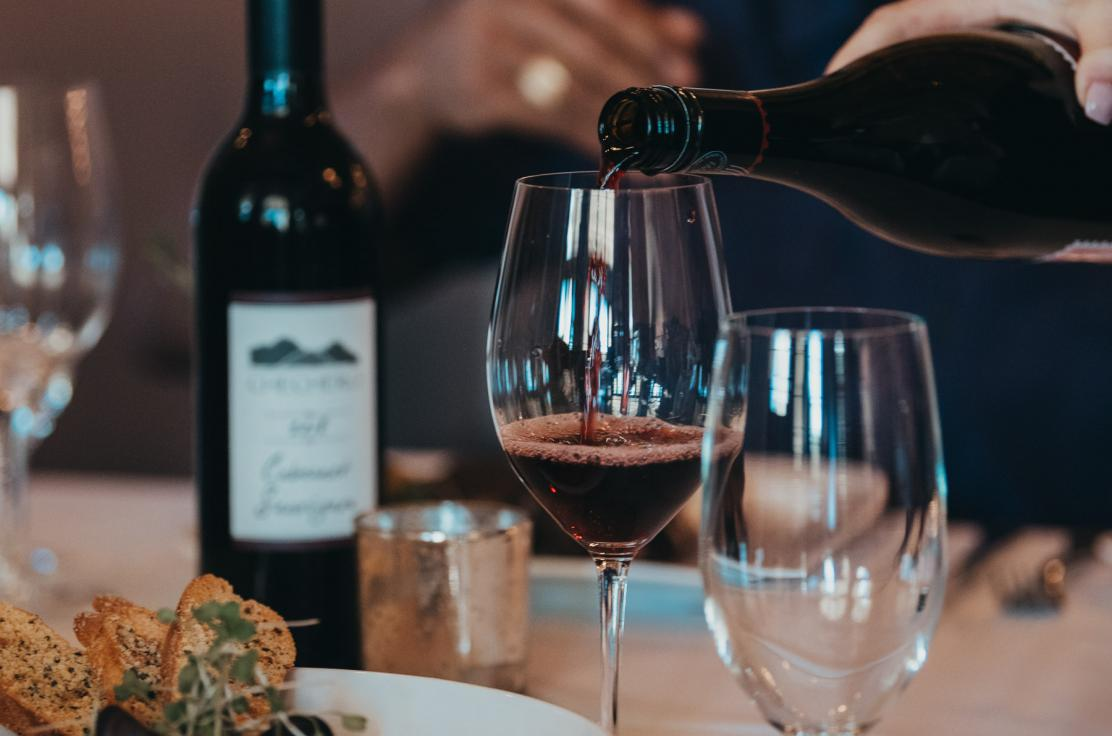 A woman's hand is shown pouring from a cabernet sauvignon bottle into a wine glass. In the background is a man's arm. In the foreground, there is a mussels and bread dish on the table.