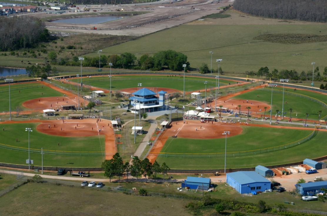 An aerial view of an outdoor sporting ground comprised of five baseball fields.