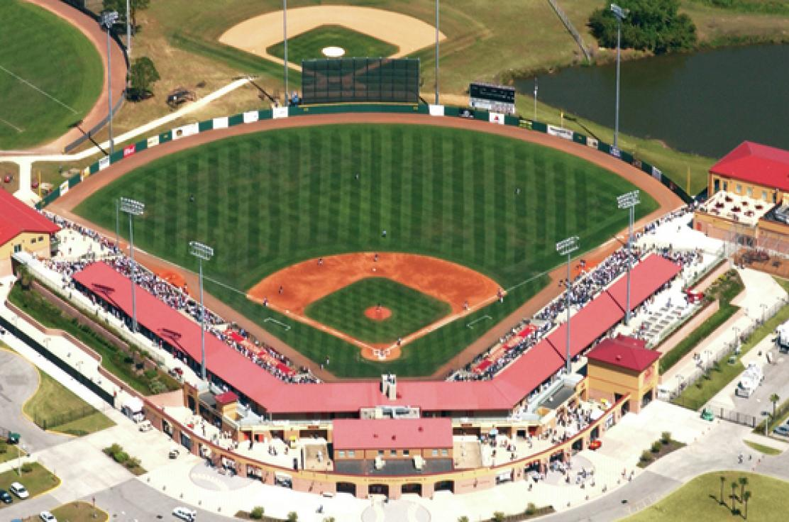 An aerial view of a baseball field filled with fans during a sunny afternoon game.
