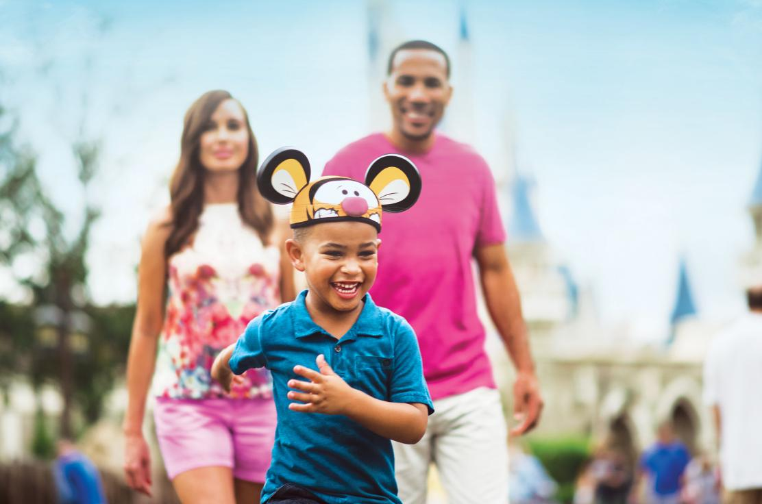 Little boy running in front of parents at Walt Disney World Resort