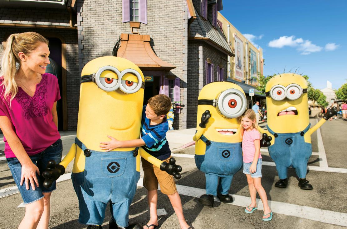 Daughter and son hugging minions with mom at Universal Studios Florida at Universal Orlando Resort