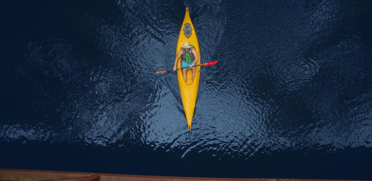 A man paddles under a bridge in Kissimmee