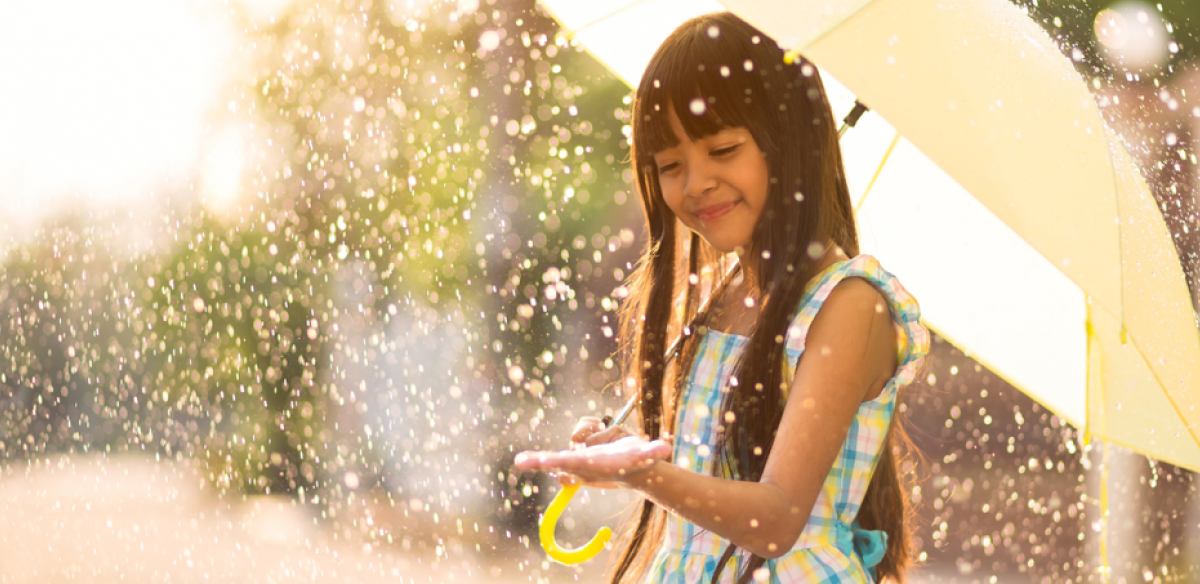 Smiling girl in a sun shower with an umbrella.