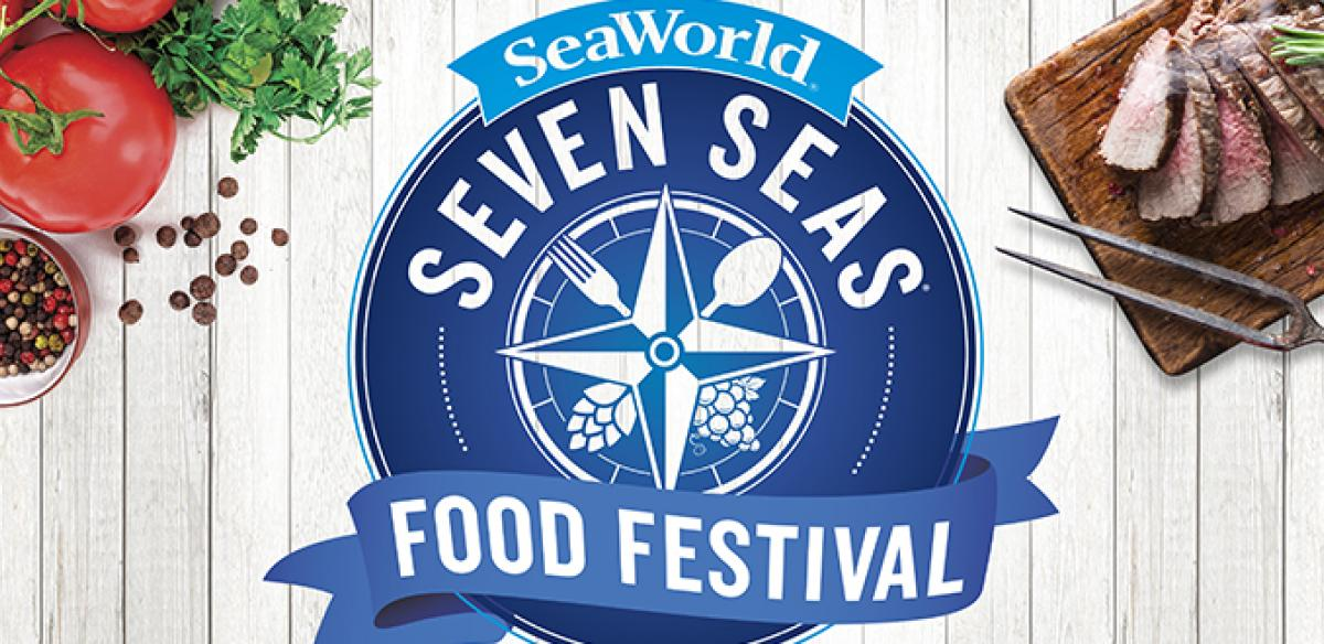 Sea World Seven Seas Food Festival logo with a blue background on top of a wooden table beside meat and vegetables.