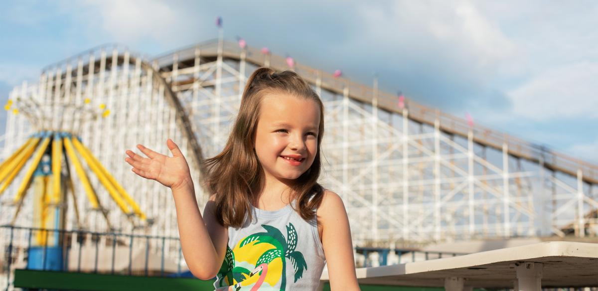 A child waves in front of a roller coaster in Kissimmee