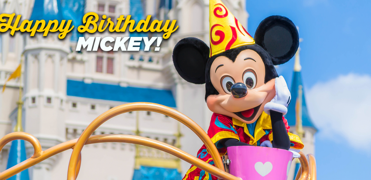 A person in a Mickey Mouse costume and birthday hat leaning on a railing with