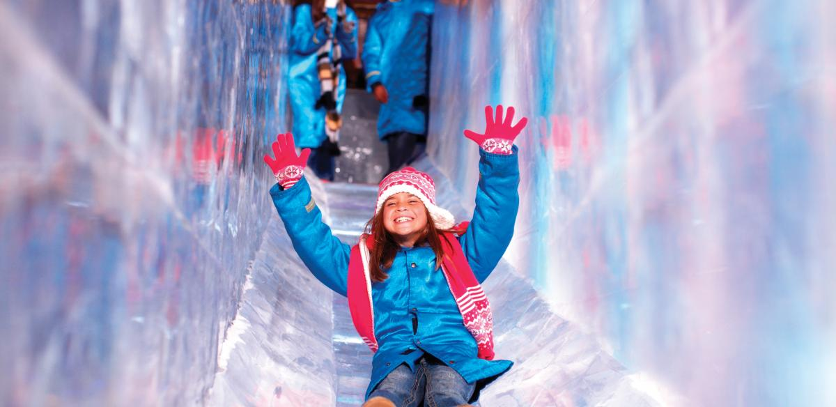 A child slides down the ice slide at ICE!