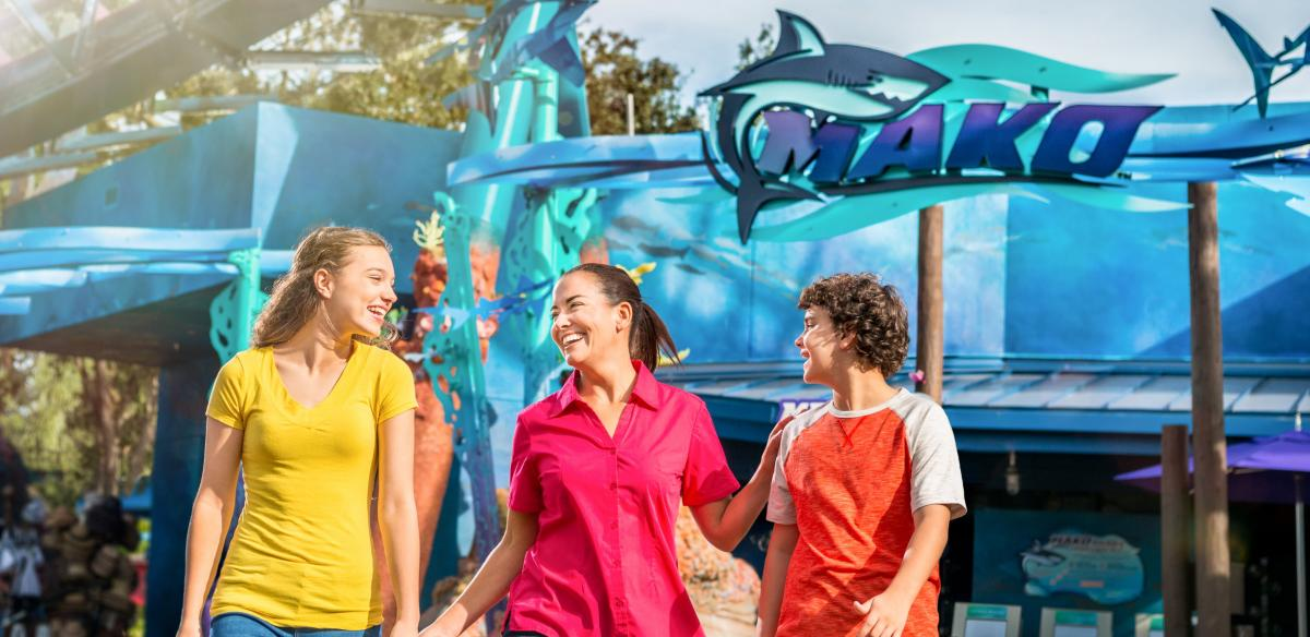 A women and two children walk in front of a rollercoaster at Sea World