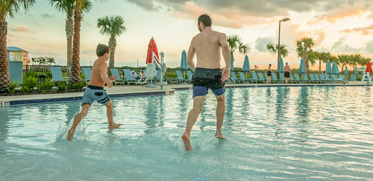 A man and child run into the pool