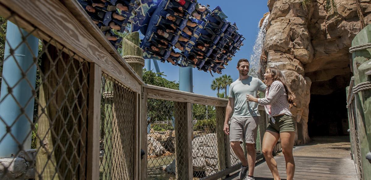 A couple walks near a rollercoaster at SeaWorld