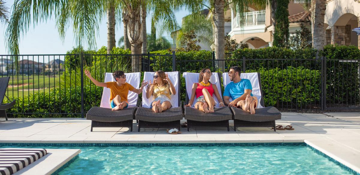 Family of four each sitting on a lounge chair by the pool
