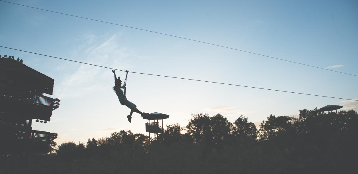 silhouette of woman on zip line at sunset