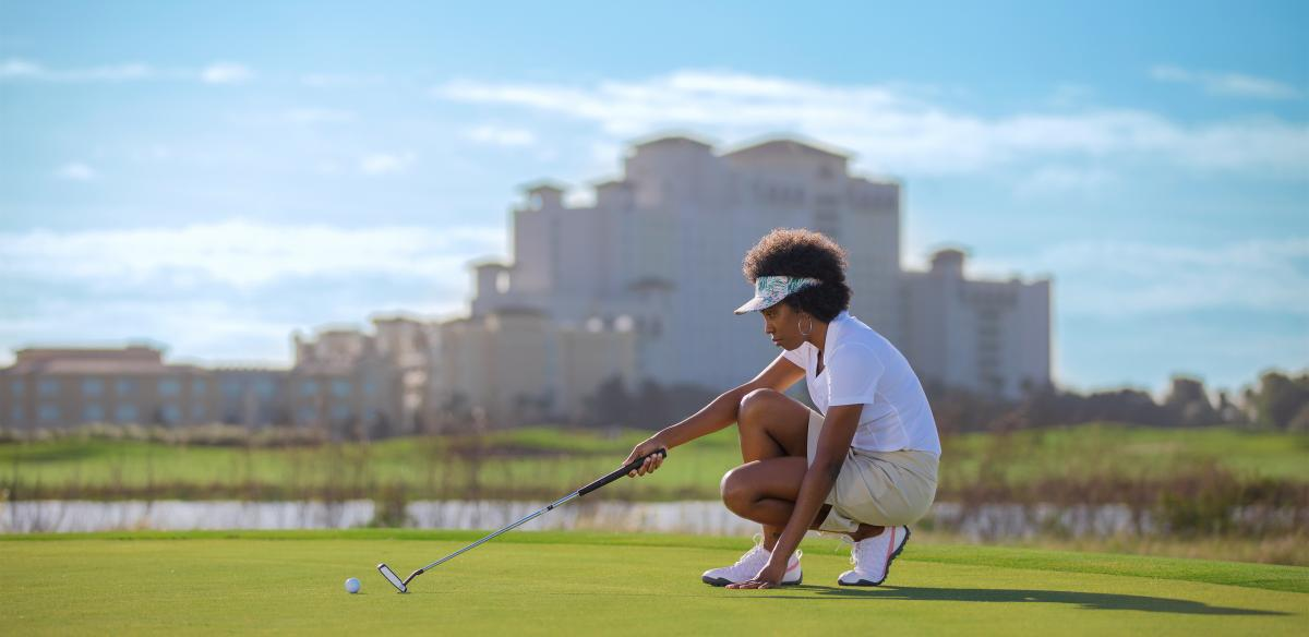 a woman playing golf outdoors