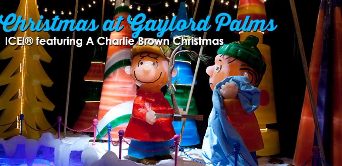 Two Charlie Brown statues in front of a Christmas set and