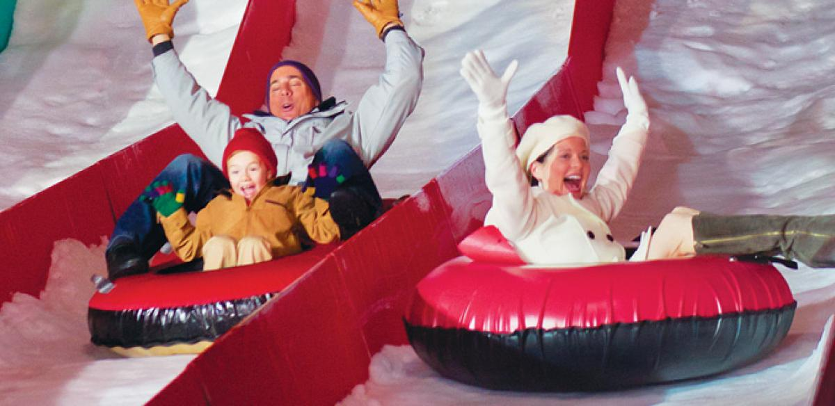 A man, woman, and young boy going down a snowy hill in blow up red and black tubes.