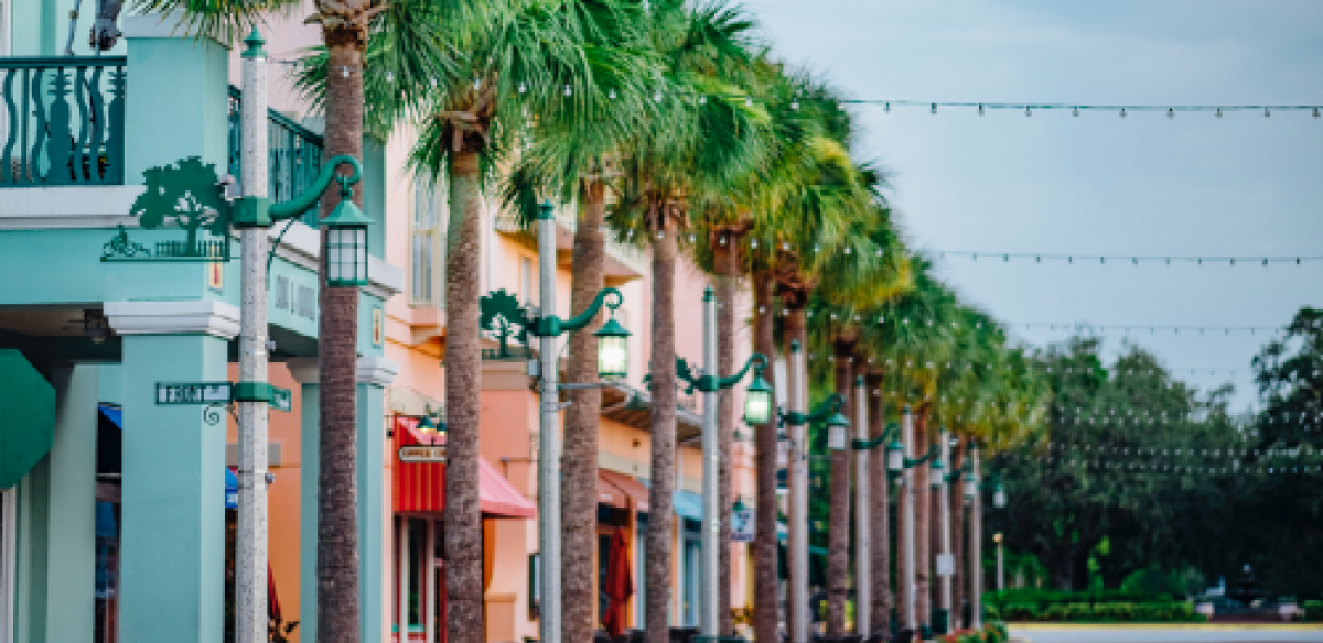 A street with multiple different colored buildings, green street lights, and tall trees in Kissimmee, Florida.