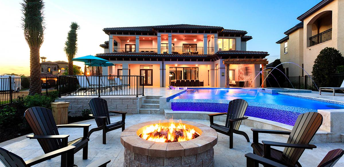 Six chairs surround a fire pit in front of a luxury accommodation at sunset in Kissimmee, Florida.
