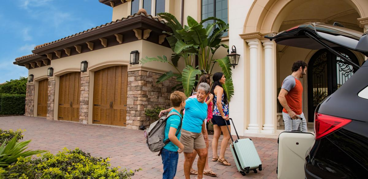 A family removes suitcases from the trunk of their car outside a vacation home in Kissimmee, Florida.