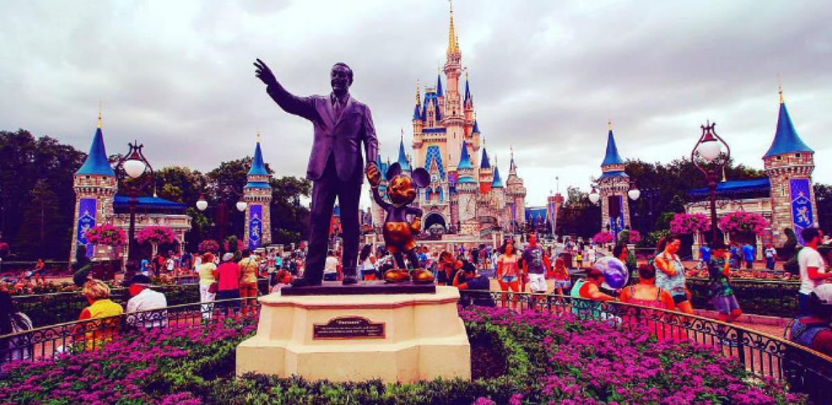 Entrance to Magic Kingdom theme park with crowds of people walking and a statue of Walt Disney and Mickey Mouse.