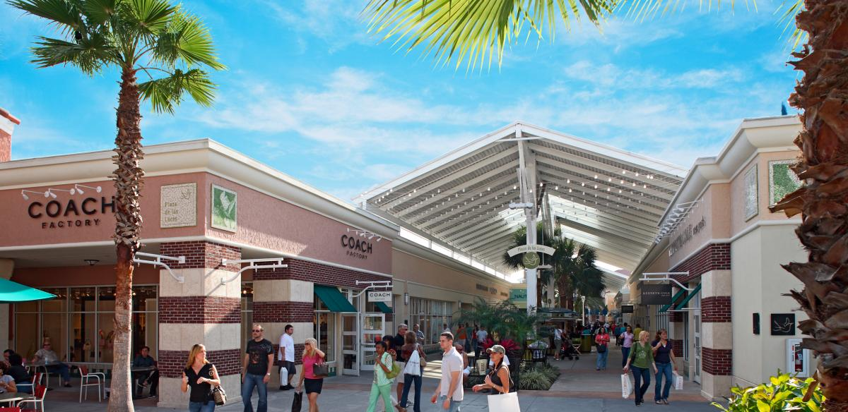 A shopping pavilion on a sunny day with a Coach store in the forefront in Kissimmee, Florida.