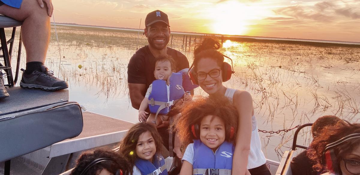 Dr. Laura and her family on an airboat at golden hour