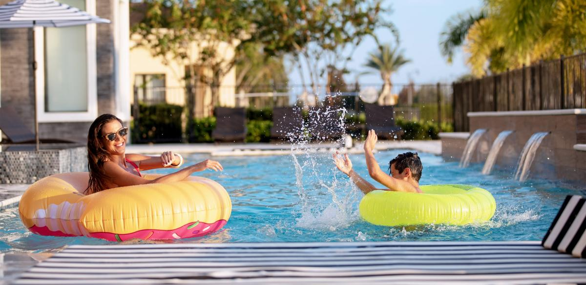Woman and child on inflatable rings at the pool