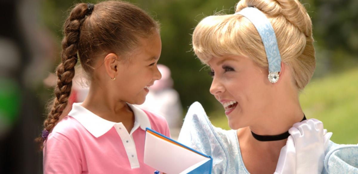 Woman dressed up as Cinderella laughing with a little girl whose holding a book on a sunny day.