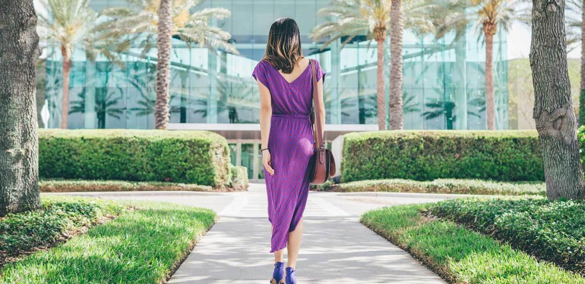 Rearview of a woman in a purple dress walking