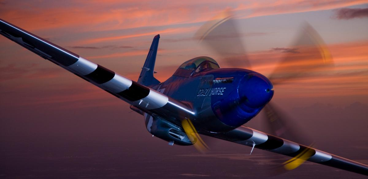 A plane named Crazy Horse flying into the sunset