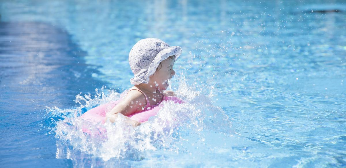 A toddler-aged girl splashes around in a swimming pool. Kissimmee, Florida, is a great spot to vacation with young kids!