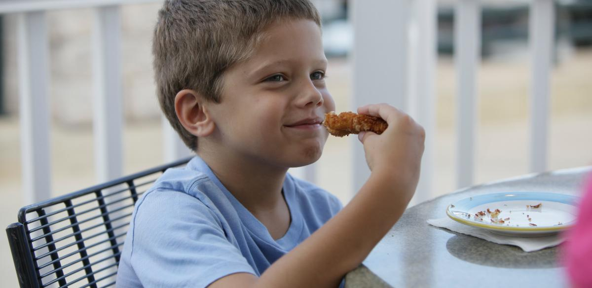 A boy enjoying his breaded shrimp