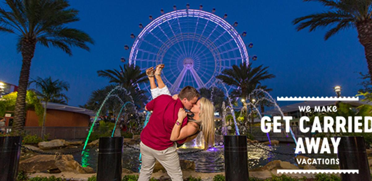 A man and woman kissing in front of a pond and ferris wheel at night with