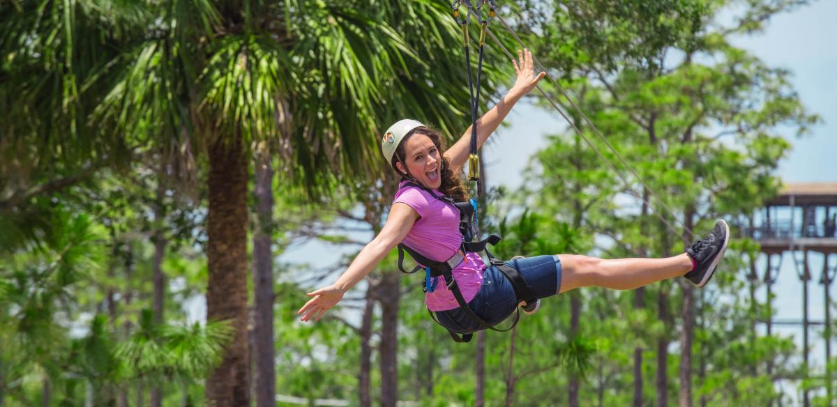 A woman ziplining through the treetops