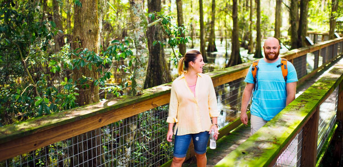 Man and woman walking along a wooden bridge in the woods.