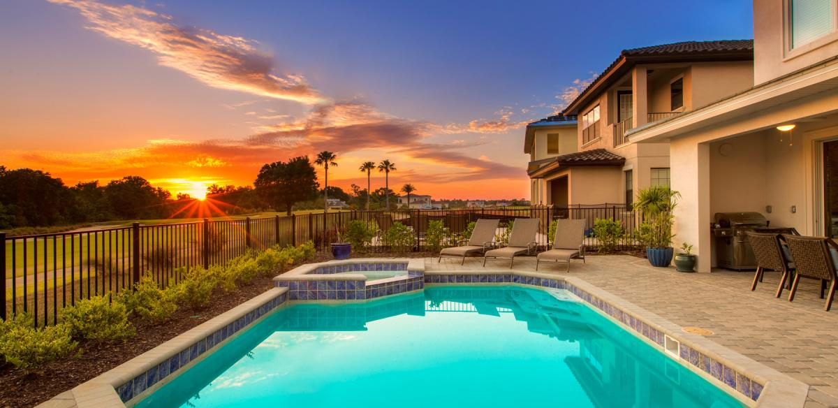 Stone patio beside a long in-ground pool, at sunset with orange, purple, and blue hues in the sky.