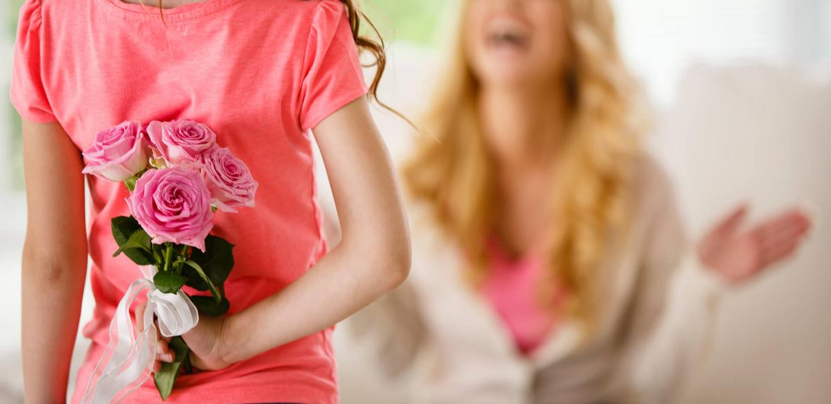 Girl giving mother flowers.