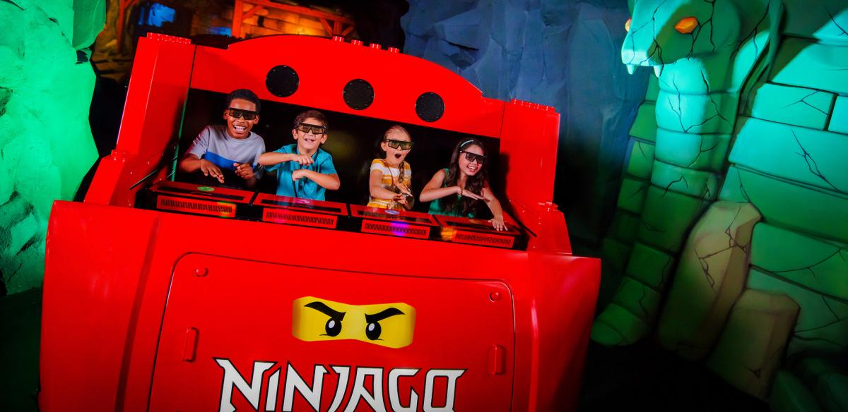 Four kids riding on a Ninjago Lego Land ride.