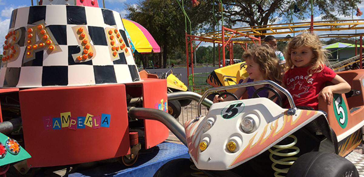Two children on a red, black, and white theme park ride in Kissimmee, Florida.