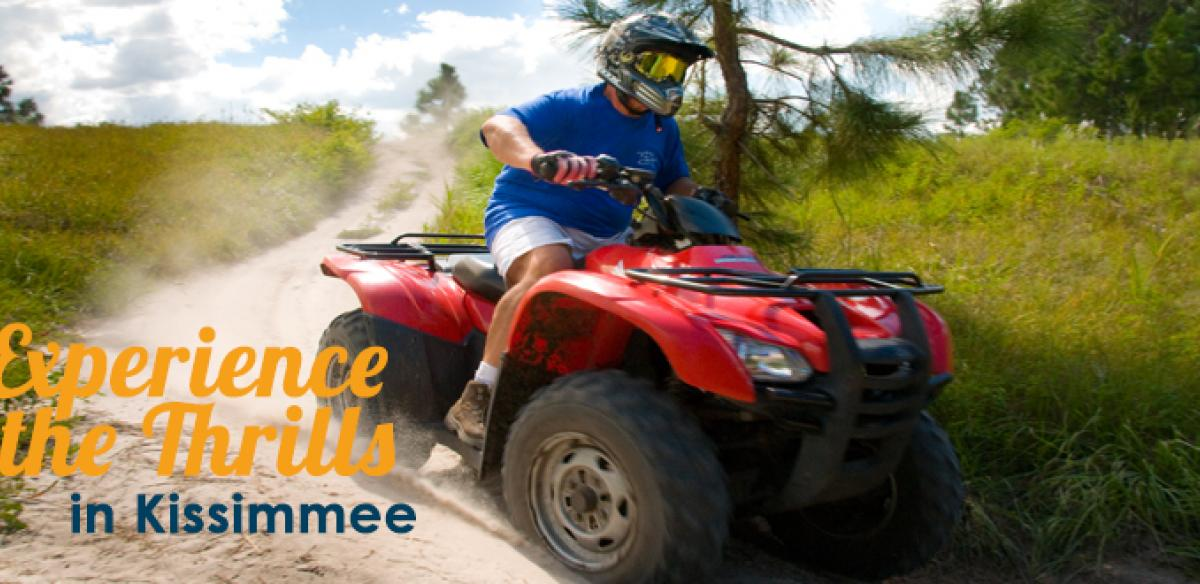 A man driving a red ATV on a dirt road around tall grass with